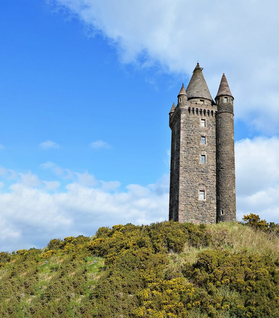 Stone tower with green grass and blue sky