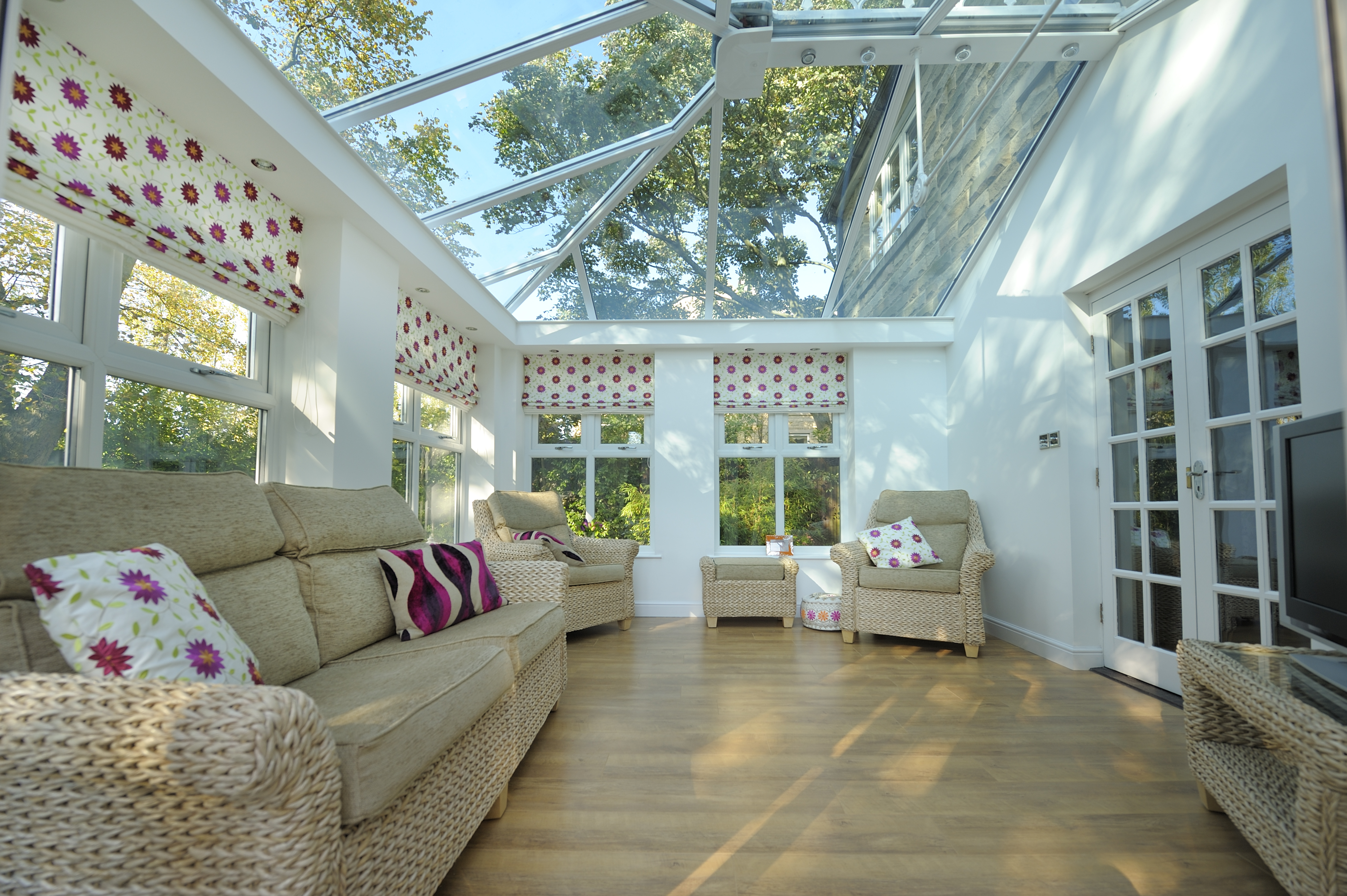 Inside a white conservatory with a glass roof.